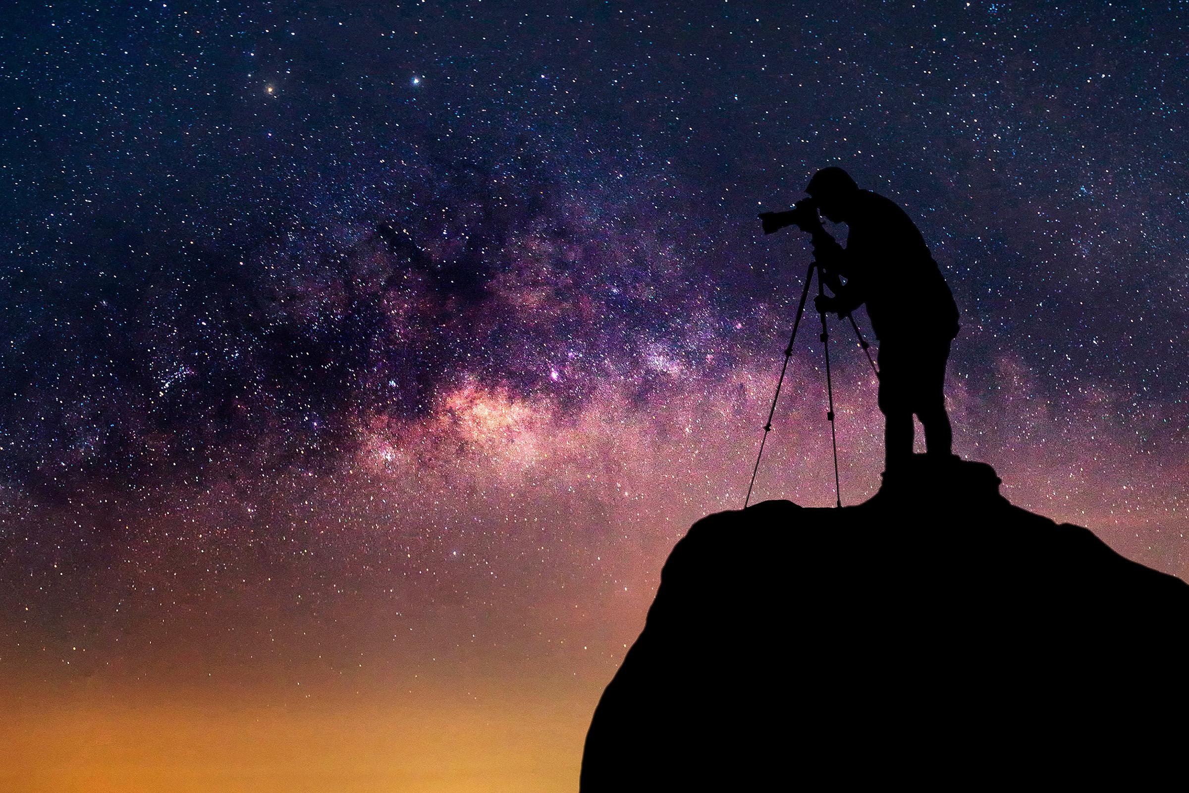 Man with camera shooting the night sky