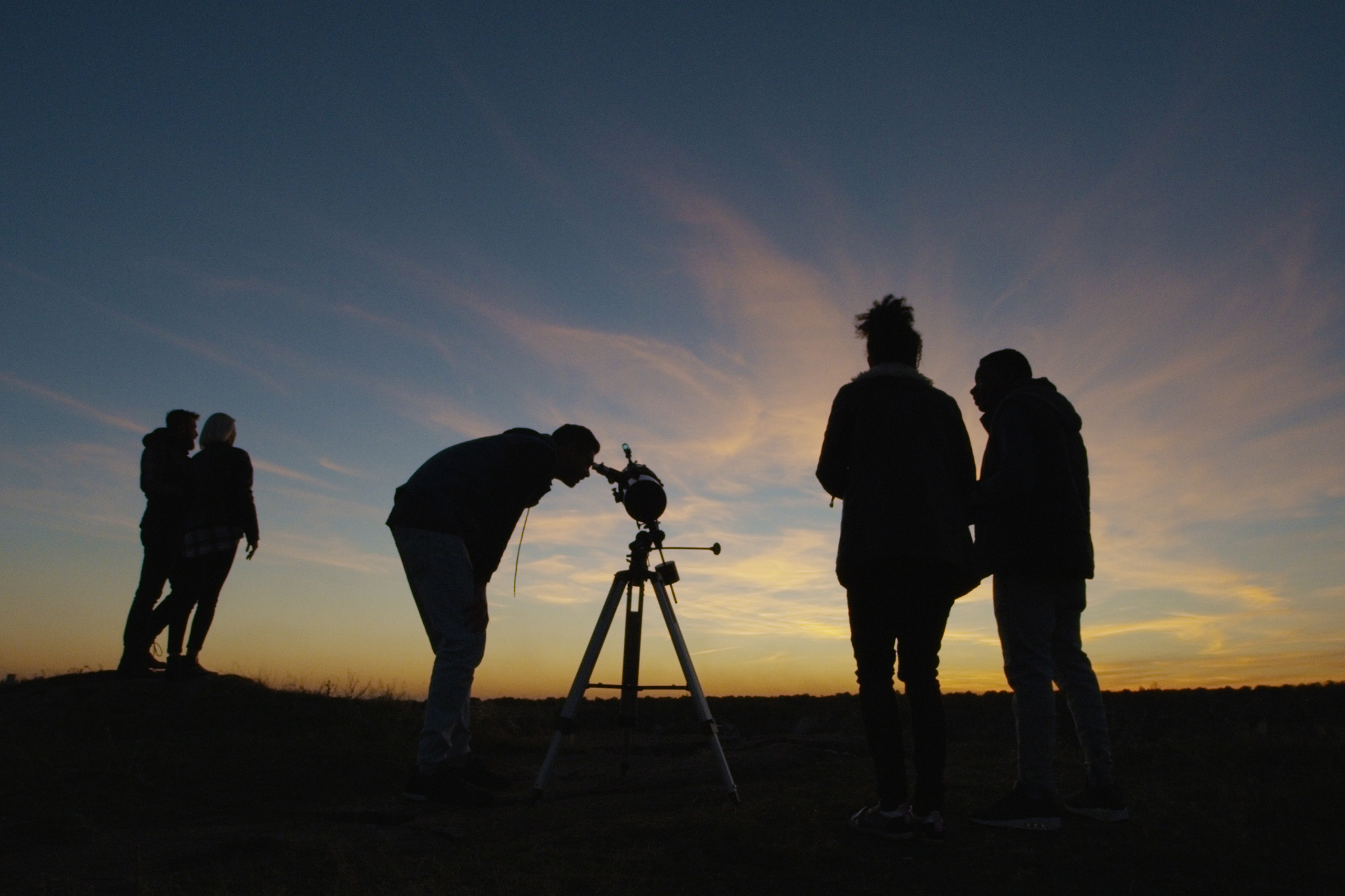 Group of people taking pictures of night sky